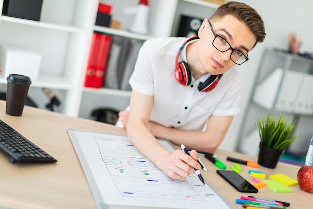 Młody mężczyzna w okularach stoi przy biurku komputerowym .ng.