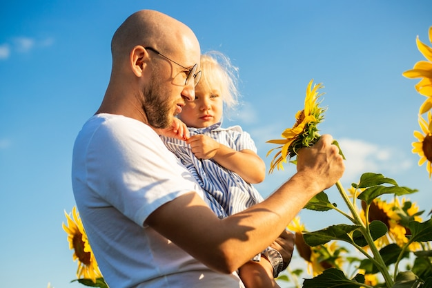 Młody mężczyzna w okularach trzyma dziecko w ramionach i patrzy na kwiaty słonecznika na słonecznikowym polu.