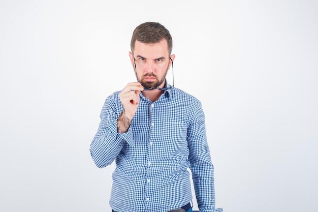 Młody mężczyzna w okularach w koszuli, dżinsach i patrząc pewnie. przedni widok.