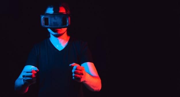 Młody mężczyzna w okularach wirtualnej rzeczywistości gra w gry wideo.