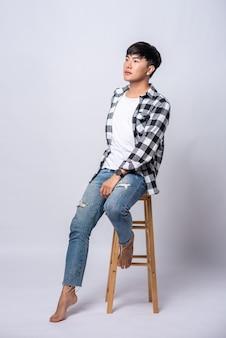 Młody mężczyzna w pasiastej koszuli siedzi na wysokim krześle.