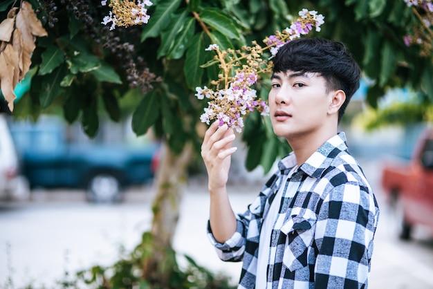 Młody mężczyzna w pasiastej koszuli stał na poboczu i trzymał kwiat.