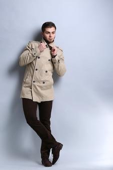 Młody mężczyzna w płaszczu na szarej ścianie