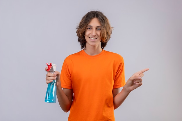 Młody mężczyzna w pomarańczowej koszulce gospodarstwa spray do czyszczenia, uśmiechając się radośnie patrząc na kamerę, wskazując na bok stojący na białym tle