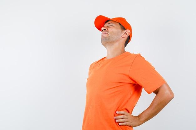Młody mężczyzna w pomarańczowej koszulce i czapce cierpi na ból pleców i wygląda na zmęczonego