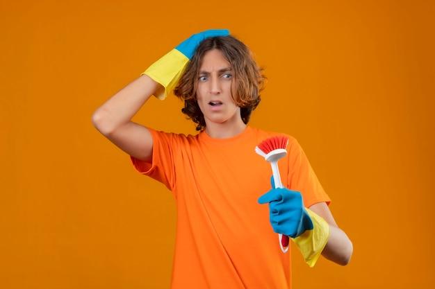 Młody mężczyzna w pomarańczowej koszulce w gumowych rękawiczkach trzyma szczotkę do szorowania patrząc na nią zaskoczony dotykając głowy stojącej na żółtym tle