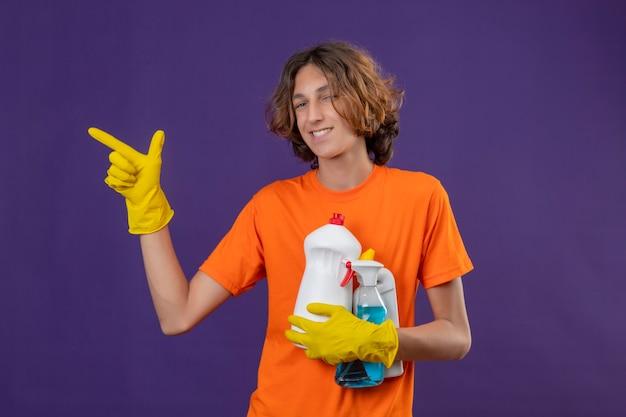 Młody mężczyzna w pomarańczowej koszulce w gumowych rękawiczkach, trzymając narzędzia do czyszczenia, wskazując na bok, uśmiechając się radośnie stojąc na fioletowym tle