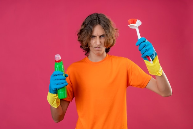 Młody mężczyzna w pomarańczowej koszulce w gumowych rękawiczkach trzymający butelkę środków czyszczących i szczoteczka do szorowania patrząc na kamerę niezadowolony z zmarszczonej twarzy stojącej na różowym tle