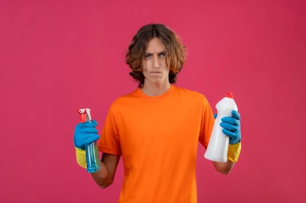 Młody mężczyzna w pomarańczowej koszulce w gumowych rękawiczkach trzymający spray do czyszczenia i butelkę środków czyszczących patrząc na kamerę niezadowolony z zmarszczonej twarzy stojącej na różowym tle