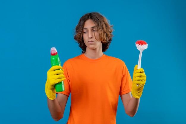 Młody mężczyzna w pomarańczowej koszulce w gumowych rękawiczkach trzymający szczotkę do szorowania i butelkę ze środkami czyszczącymi wyglądający na niepewnego i mającego wątpliwości stojąc na niebieskim tle