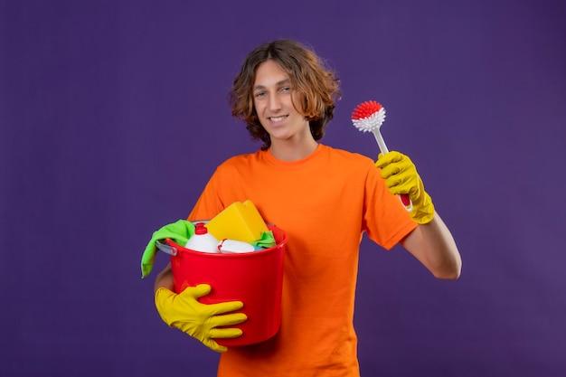 Młody mężczyzna w pomarańczowej koszulce w gumowych rękawiczkach trzymający wiadro z narzędziami do czyszczenia i szczotką do szorowania patrząc na kamerę uśmiechnięty wesoło stojąc na fioletowym tle