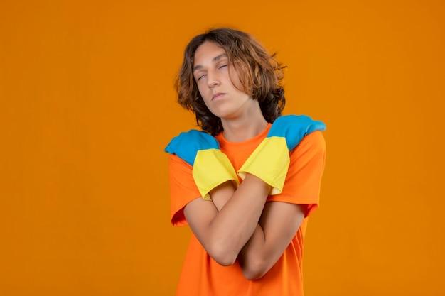 Młody mężczyzna w pomarańczowej koszulce w gumowych rękawiczkach, tulący się z zamkniętymi oczami, stojący na żółtym tle