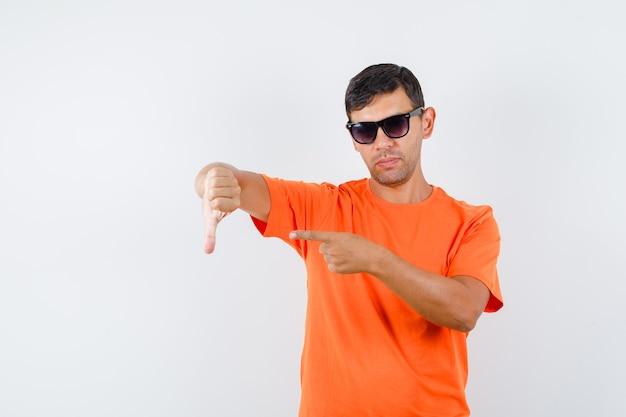 Młody mężczyzna w pomarańczowej koszulce, wskazując na kciuk w dół