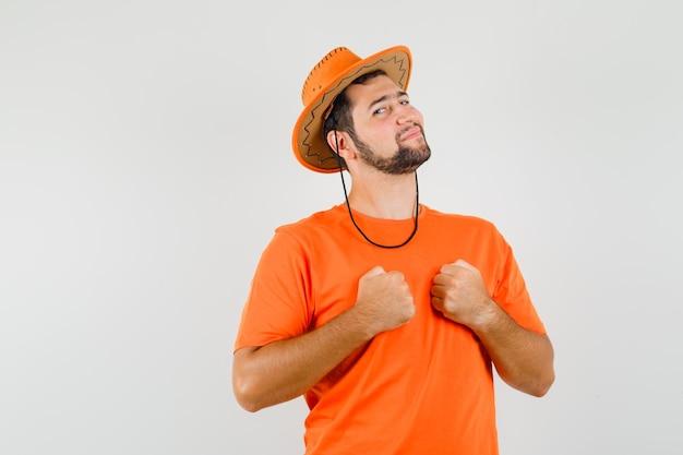 Młody mężczyzna w pomarańczowym t-shircie, kapeluszu trzymającym zaciśnięte pięści na klatce piersiowej i wyglądającym pewnie, widok z przodu.