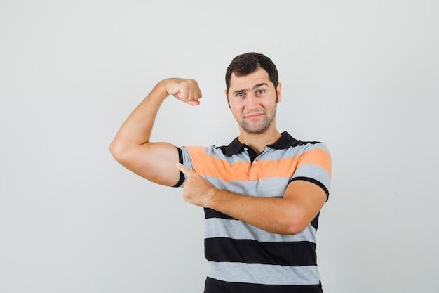 Młody mężczyzna w prążkowanej koszulce, ukazujący mięśnie ramion i wyglądający na potężnego