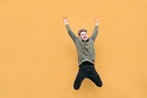 Młody mężczyzna w przypadkowych ubraniach skacze na pomarańczowej ścianie.