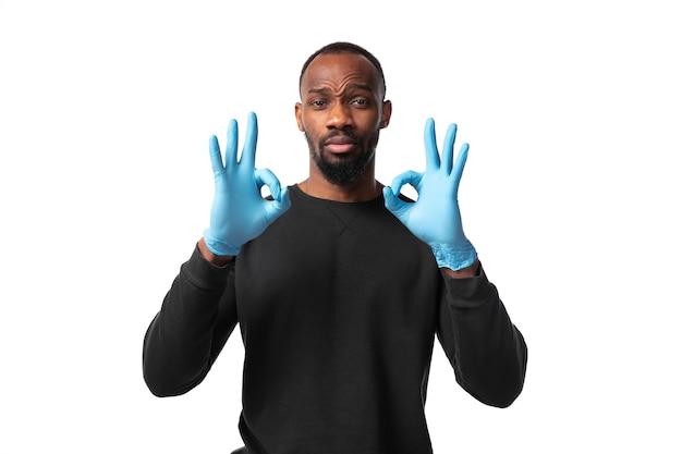 Młody mężczyzna w rękawiczkach pokazujący ok gest