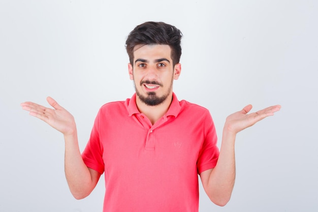 Młody mężczyzna w różowej koszulce dokonywanie gestu wagi i patrząc pewnie, widok z przodu.