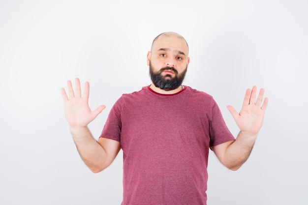 Młody mężczyzna w różowej koszulce pokazuje nie znam gestu, widok z przodu.