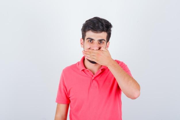 Młody mężczyzna w różowej koszulce, trzymając rękę na ustach i patrząc wesoło, widok z przodu.