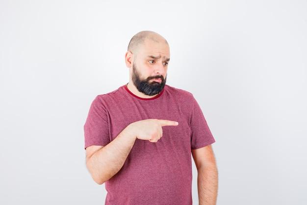 Młody mężczyzna w różowej koszulce, wskazując na bok i patrząc shied, widok z przodu.