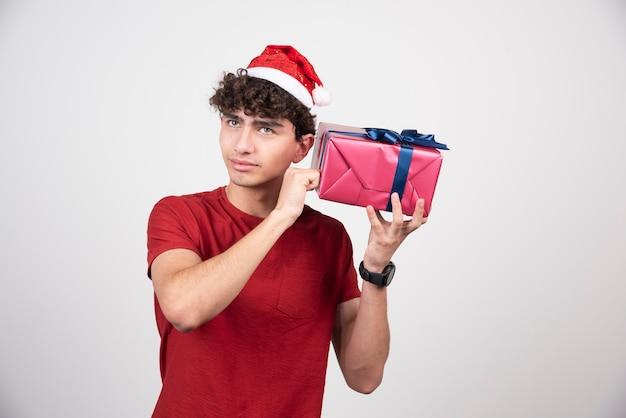 Młody mężczyzna w santa hat próbuje dowiedzieć się, co jest w pudełku.