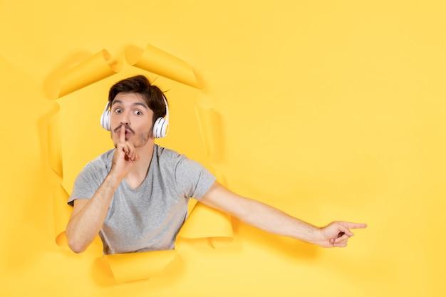 Młody mężczyzna w słuchawkach na rozdartym żółtym papierze w tle dźwięki ultradźwiękowe