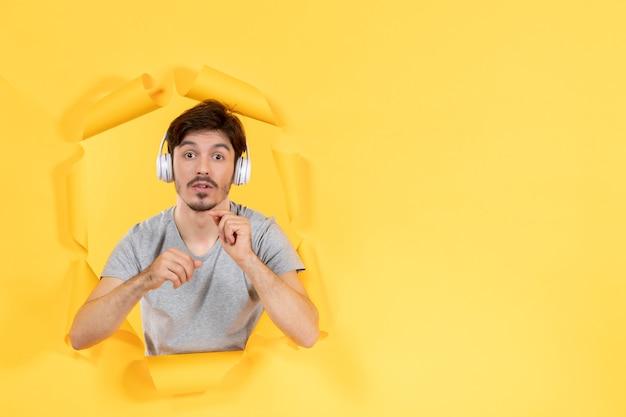Młody mężczyzna w słuchawkach na żółtym papierze dźwięki ultradźwięków w tle