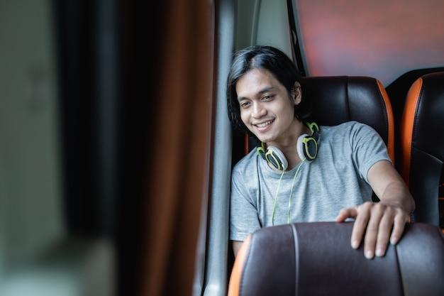 Młody mężczyzna w słuchawkach siedzi przy oknie i spogląda na autobus