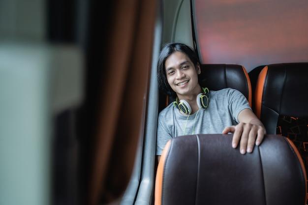 Młody mężczyzna w słuchawkach uśmiecha się do kamery siedząc przy oknie w autobusie