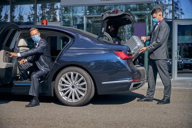 Młody mężczyzna w sterylnej masce pakuje bagaż szefa do bagażnika, gdy wsiada do samochodu