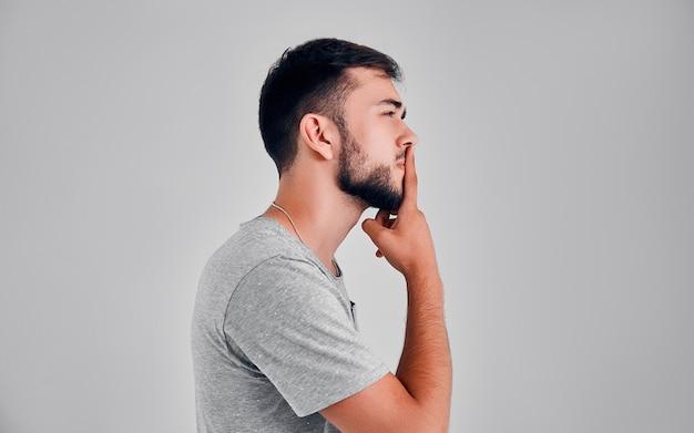 Młody mężczyzna w studiu myśli na szarym tle, kładąc palec na ustach