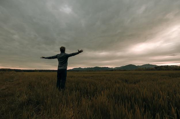 Młody mężczyzna w swetrze i dżinsach stoi na jesiennej łące pod niebem grzmotu z szeroko rozłożonymi rękami.