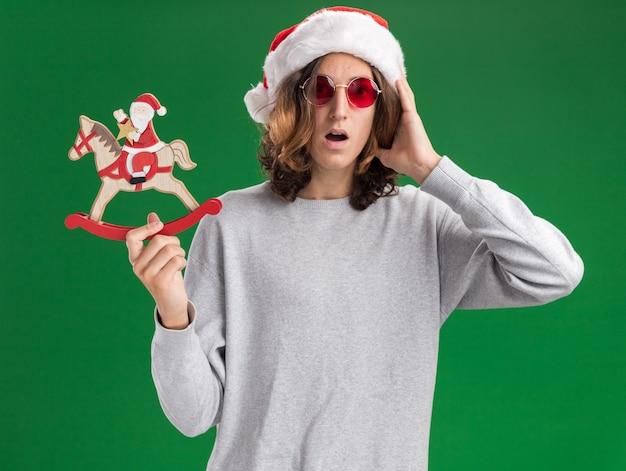 Młody mężczyzna w świątecznej czapce mikołaja i czerwonych okularach trzymający bożonarodzeniową laskę cukrową zdumiony i zaskoczony stojąc nad zieloną ścianą