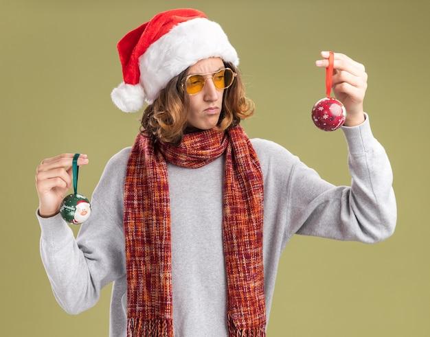 Młody mężczyzna w świątecznym czapce mikołaja i żółtych okularach z ciepłym szalikiem na szyi trzyma bombki wyglądające na zdezorientowanego próbując dokonać wyboru stojąc na zielonym tle