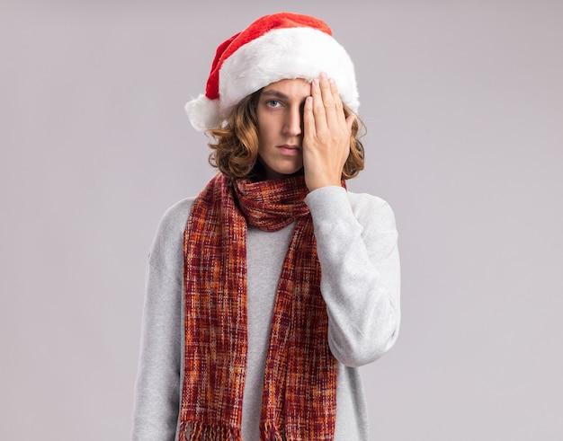 Młody mężczyzna w świątecznym czapce mikołaja z ciepłym szalikiem na szyi patrząc na kamerę z poważną twarzą zakrywającą jedno oko ręką stojącą na białym tle