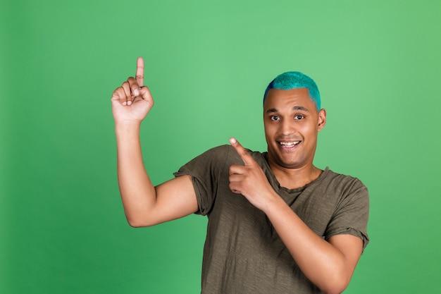 Młody mężczyzna w swobodnym stylu na zielonej ścianie, niebieskie włosy wskazują palcem w górę