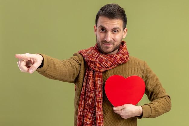 Młody mężczyzna w swobodnym ubraniu z szalikiem na szyi trzymający serce z kartonu wskazujący palcem wskazującym na bok uśmiechnięty pewny siebie walentynkowy koncept stojący nad zieloną ścianą