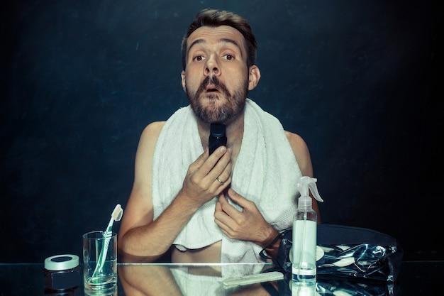 Młody mężczyzna w sypialni, siedzący przed lustrem, drapiąc się w brodę w domu