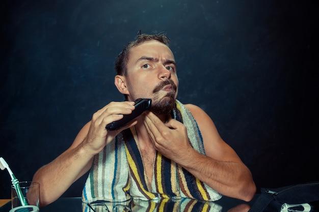 Młody mężczyzna w sypialni siedzi przed lustrem drapiąc się po brodzie w domu
