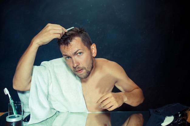 Młody mężczyzna w sypialni siedzi przed lustrem drapiąc się po brodzie