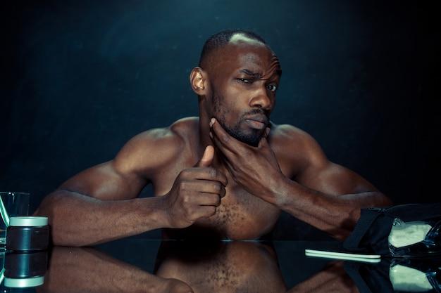 Młody mężczyzna w sypialni siedzi przed lustrem po podrapaniu się po brodzie