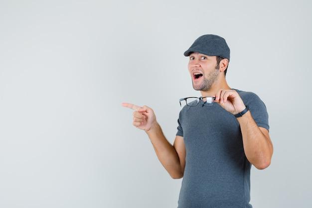 Młody mężczyzna w szarej czapce t-shirt, trzymając okulary, wskazując na bok i patrząc na szczęśliwego