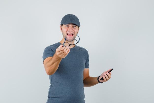 Młody mężczyzna w szarej czapce t-shirt, trzymając telefon komórkowy i okulary i patrząc wesoło