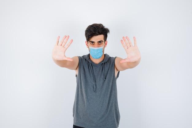 Młody mężczyzna w szarej koszulce noszący maskę, podnosząc dłonie w geście kapitulacji i wyglądając poważnie