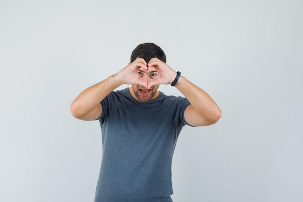 Młody mężczyzna w szarej koszulce pokazuje gest serca