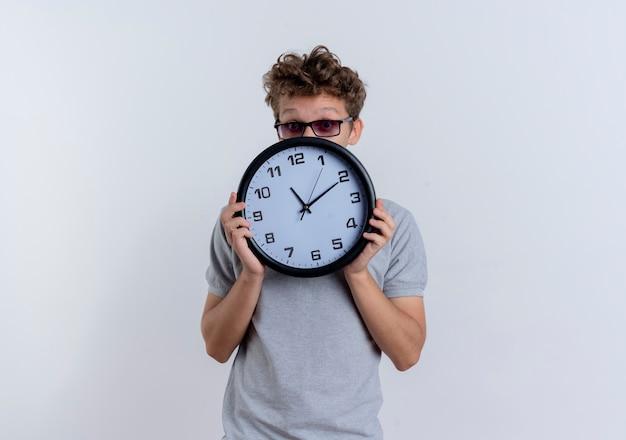 Młody mężczyzna w szarej koszulce polo trzyma zegar ścienny, ukrywając twarz zerkającą na zaskoczonego stojącego nad białą ścianą