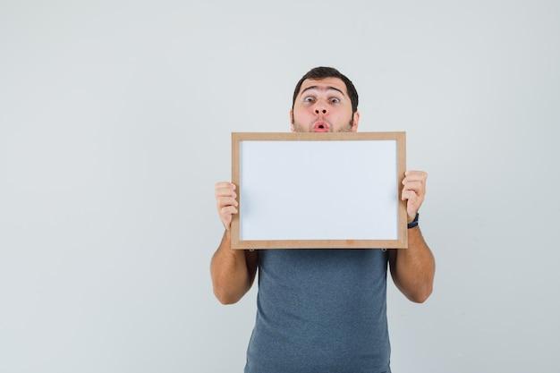 Młody mężczyzna w szarej koszulce, trzymając pustą ramkę i wyglądający na zaskoczonego