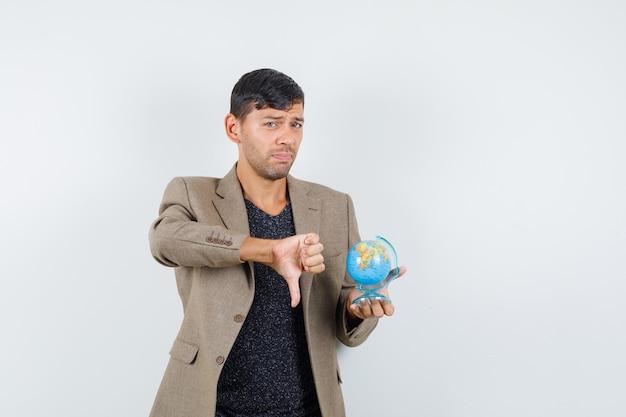 Młody mężczyzna w szaro-brązowej kurtce, czarnej koszuli, trzymający mini kulę ziemską, pokazujący kciuk w dół i niezadowolony, widok z przodu.