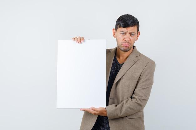 Młody mężczyzna w szaro-brązowej kurtce stojącej z trzymając czysty papier i patrząc smutno, widok z przodu.
